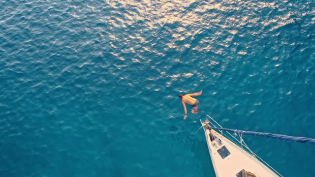 4k aerial drone point of view man jumping off sailboat into sunny, blue ocean, real time - nautical vessel stock videos & royalty-free footage