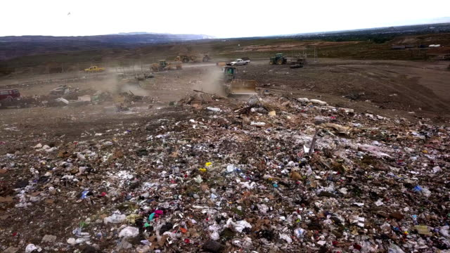 ごみを掻き取るトラクターと商業埋立地のごみ捨て場の視点の空中ドローン - ゴミ収集車点の映像素材/bロール