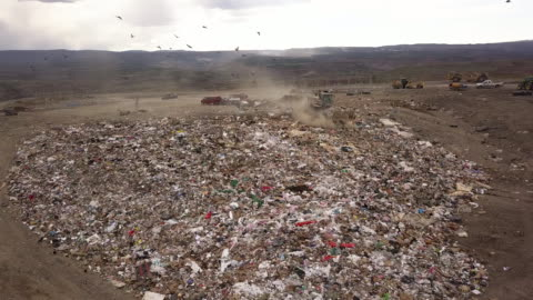 aerial drone point of view of a commercial landfill garbage dump with tractors scraping the trash - scavenging stock videos & royalty-free footage