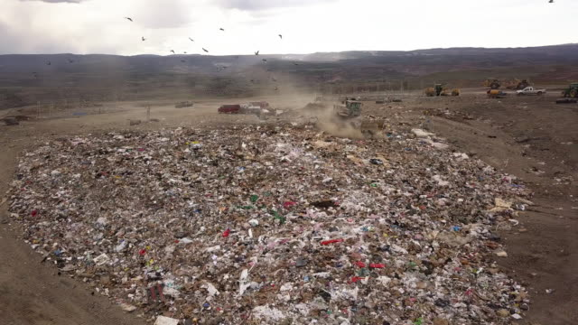 aerial drone point of view of a commercial landfill garbage dump with tractors scraping the trash - landfill stock videos & royalty-free footage