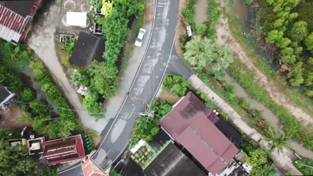 田舎の風景に沿った地元の道路の空中ドローンの視点 - village点の映像素材/bロール