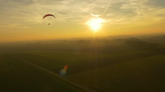 vídeos de stock e filmes b-roll de aerial drone point of view paraglider parachuting over sunny, idyllic rural landscape, real time - eslovénia