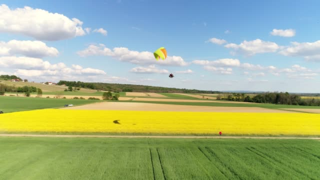 Aerial drone point of view paraglider with parachute over rural landscape, real time
