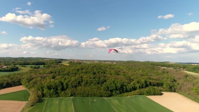 日当たりの良い農村風景、リアルタイムにパラシュートで空中ドローンの視点パラグライダー - パラグライディング点の映像素材/bロール