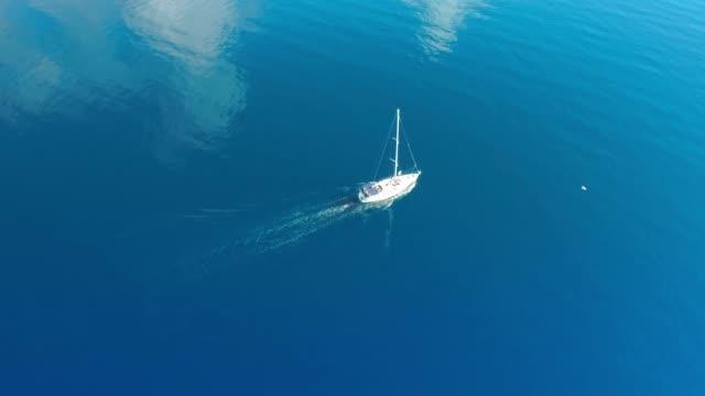 日当たりの良い静かな青い海、リアルタイムで 4 k 空中ドローンの視点ヨット - ブラック島点の映像素材/bロール