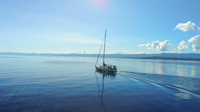 4k aerial drone point of view sailboat on tranquil sunny blue ocean, real time - sailor stock videos & royalty-free footage