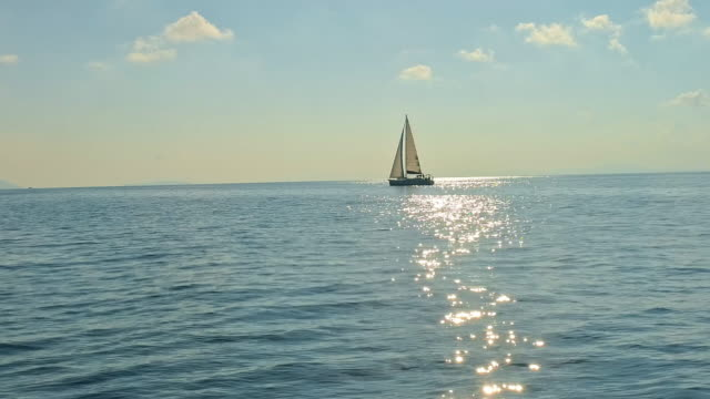 4k aerial drone point of view sailboat on tranquil, sunny blue ocean, real time - yacht stock videos & royalty-free footage