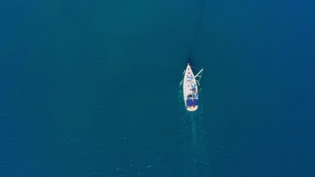 4k aerial drone point of view sailboat on tranquil, sunny blue ocean, real time - sailing boat stock videos & royalty-free footage