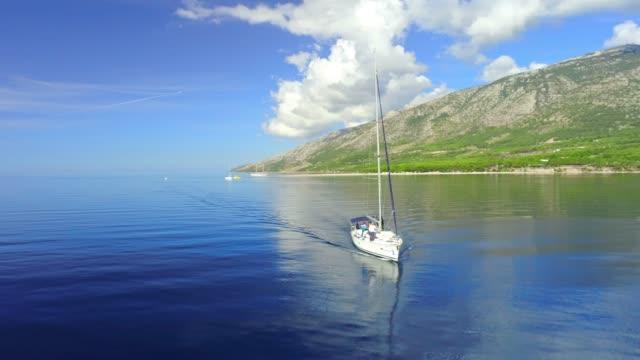 日当たりの良い、静かな青い海、リアルタイムで 4 k 空中ドローンの視点ヨット - ブラック島点の映像素材/bロール