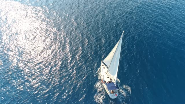 4K Aerial drone point of view sailboat on tranquil, sunny blue ocean, real time