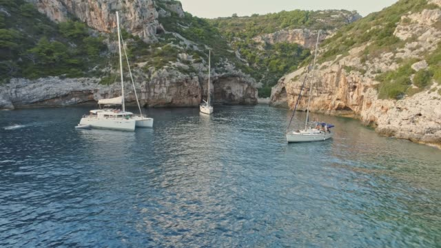4K Aerial drone point of view sailboats mooring in tranquil bay, real time