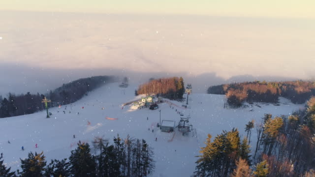 4K Aerial drone point of view skiers skiing on idyllic, snowy ski slope, real time