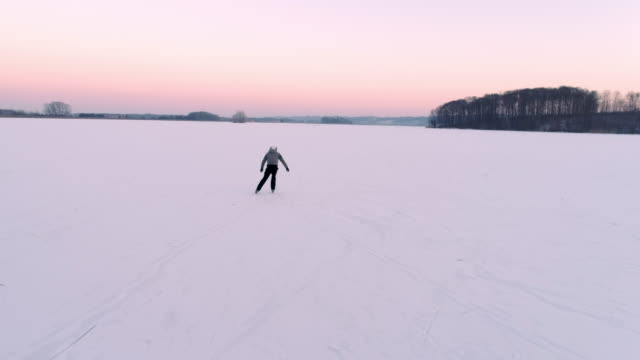 4K Aerial drone point of view teenage boy ice skating on vast, tranquil frozen lake, real time