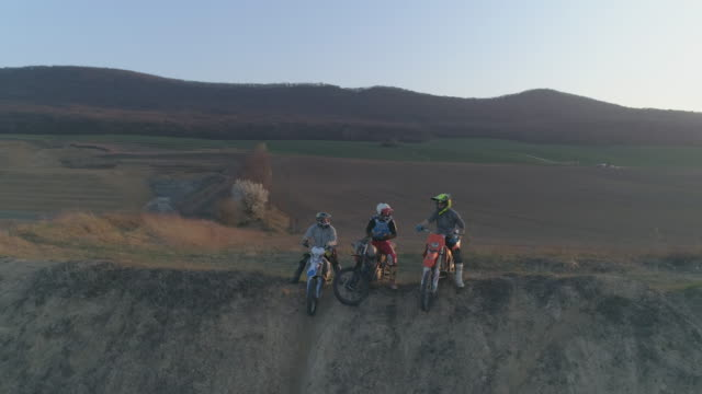 Aerial drone portrait view of men riding motocross motorcycles on a dirt off road at sunset. - Slow Motion