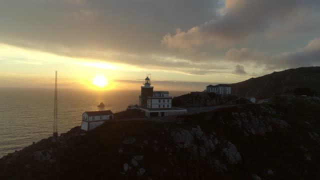 vídeos y material grabado en eventos de stock de aerial: drone reversing from cape finisterre lighthouse on mountain against sun diving into sea during sunset - galicia
