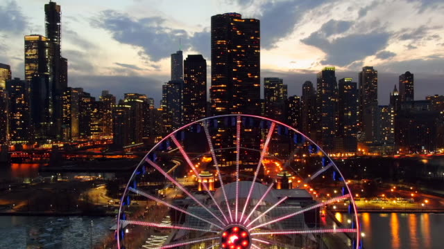 aerial: drone reversing over illuminated ferris wheel navy pier chicago against modern skyscrapers, city against sky at night - ferris wheel stock videos & royalty-free footage