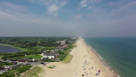 vidéos et rushes de aerial: drone reversing over people relaxing at beach by houses on sunny day against blue sky - the hamptons, ny - long island