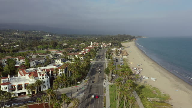 aerial: drone reversing over vehicles on street amidst beach and buildings against sky - santa barbara, california - santa barbara bildbanksvideor och videomaterial från bakom kulisserna