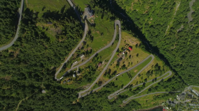 aerial: drone rotating over vehicles traveling on winding road amidst greenery on mountain with houses during sunny day - geiranger fjord, norway - zigzag stock videos & royalty-free footage