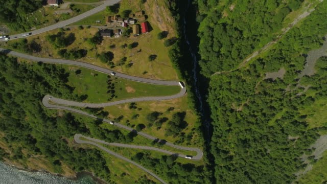 aerial: drone rotating over winding road amidst greenery on mountain during sunny day - geiranger fjord, norway - ジグザグ点の映像素材/bロール