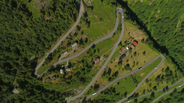 aerial: drone rotating over zigzag road amidst greenery on mountain during sunny day - geiranger fjord, norway - zigzag stock videos & royalty-free footage