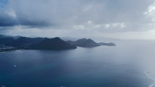 aerial drone shoots mountains with a city at the foot of the sea coast with yachts on a cloudy day (rodney bay, saint lucia) - st. lucia stock videos & royalty-free footage