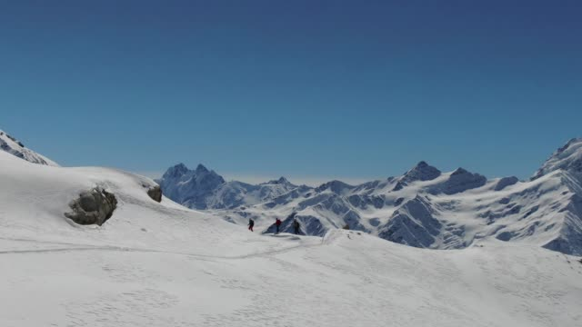 aerial drone shot circling a group of skiers standing on the edge of a mountain looking at mount elbrus - winter sport stock videos & royalty-free footage