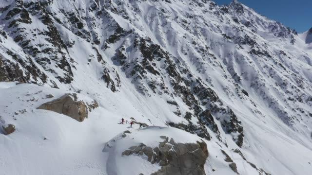 エルブルス山を見て山の端に立っているスキーヤーのグループを周回する空中ドローンショット - 辺縁部点の映像素材/bロール