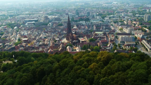 aerial drone shot near an old town with gothic church near freiburg - baden wurttemberg stock videos and b-roll footage