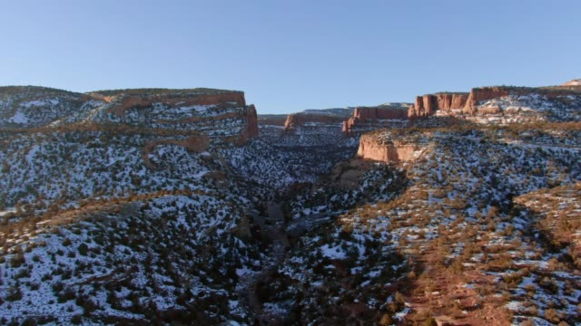 aerial drone shot near the colorado national monument and rock formations near grand junction, colorado on a sunny, winter morning - mesa stock videos and b-roll footage
