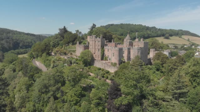aerial drone shot of 11th-century dunster castle, a country house which was formerly a motte and bailey castle near minehead, england, united kingdom. - etwa 11. jahrhundert stock-videos und b-roll-filmmaterial