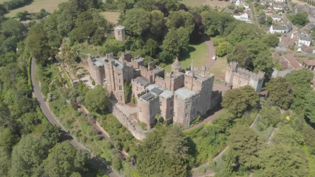 aerial drone shot of 11th-century dunster castle, a country house which was formerly a motte and bailey castle near minehead, england, united kingdom. - circa 11th century stock videos & royalty-free footage