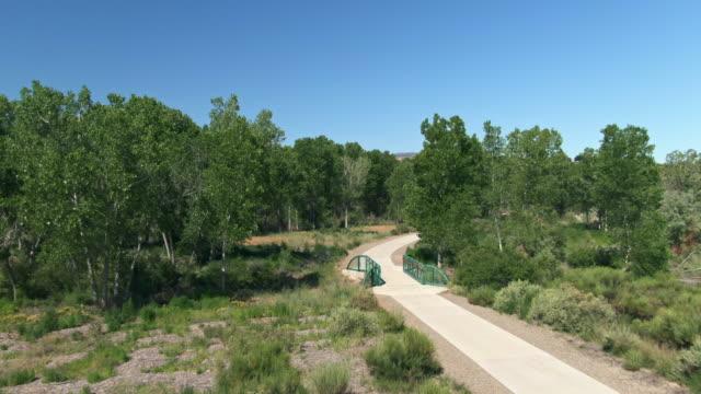 aerial drone skott av en cykelväg i den höga öknen i västra colorado (grand junction) omgiven av träd under en klar, blå himmel - scenics bildbanksvideor och videomaterial från bakom kulisserna