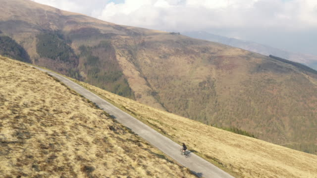 aerial drone shot of a biker riding along a mountainside - solo uomini giovani video stock e b–roll
