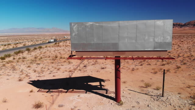 aerial drone shot of a blank, abandoned billboard advertisement by the side of interstate 15 in the utah desert under a clear, blue sky - tabellone video stock e b–roll