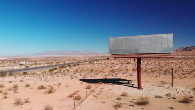 aerial drone shot of a blank, abandoned, empty billboard advertisement by the side of interstate 15 in the utah desert under a clear, blue sky - tabellone video stock e b–roll