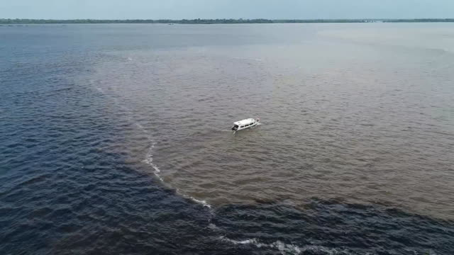 vídeos de stock, filmes e b-roll de aerial drone shot of a boat at the òmeeting of the watersó where the negro river converges with the solimoes river in brazil - aerial or drone pov or scenics or nature or cityscape