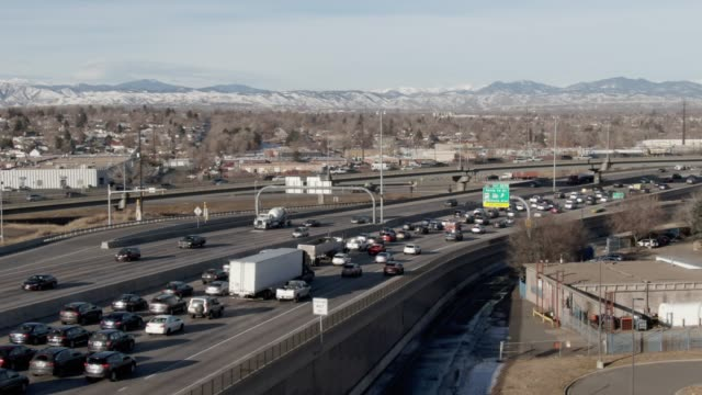 vídeos de stock e filmes b-roll de aerial drone shot of a busy interstate 70 overpass in denver on a sunny morning with the rocky mountains in the background - denver