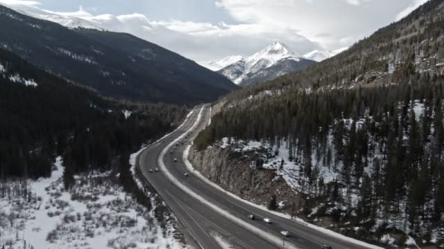 aerial drone shot of a cars and vehicles driving on interstate 70 in the rocky mountains of colorado on a snowy, partially cloudy but sunny winter day - colorado stock videos & royalty-free footage