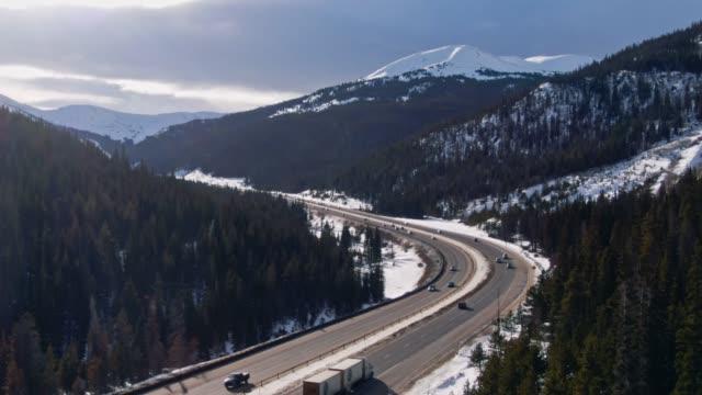 stockvideo's en b-roll-footage met luchtfoto drone shot van een auto's en voertuigen die rijden op 70 tusen staten in de rocky mountains van colorado op een besneeuwde, gedeeltelijk bewolkt maar zonnige winterdag - interstate snelweg amerika