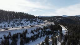 Aerial Drone Shot of a Cars and Vehicles Driving on Interstate 70 in the Rocky Mountains of Colorado on a Snowy, Partially Cloudy but Sunny Winter Day