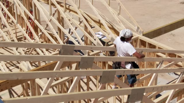 Aerial Drone Shot of a Caucasian Male Construction Worker in His Forties Framing a House on a Sunny Day