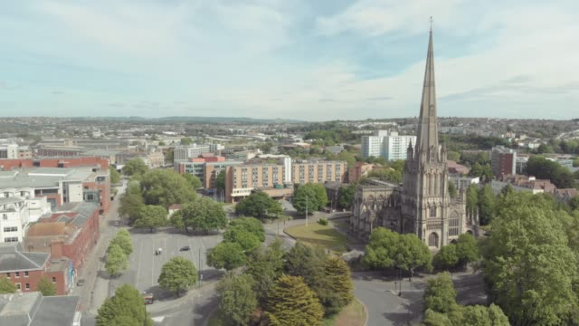 aerial drone shot of a church in the centre of bristol during the coronavirus / covid19 pandemic, with empty streets and car parks visible. - bristol inghilterra video stock e b–roll