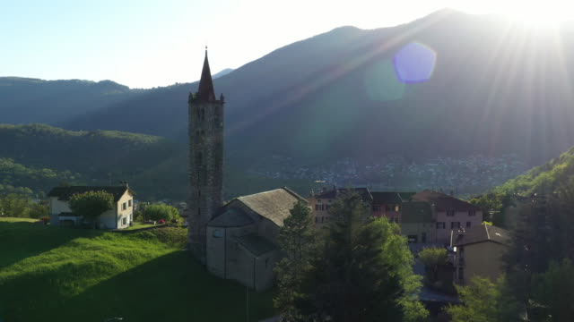 vídeos de stock e filmes b-roll de aerial drone shot of a church with sun behind - switzerland