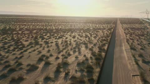 遠くの山々を背景にしたカリフォルニア/メキシコ砂漠の晴れた午後に、メキシコと米国の間のスチールスラット国境の壁と平行に走る未舗装道路の空中ドローンショット - バハカリフォルニア点の映像素材/bロール