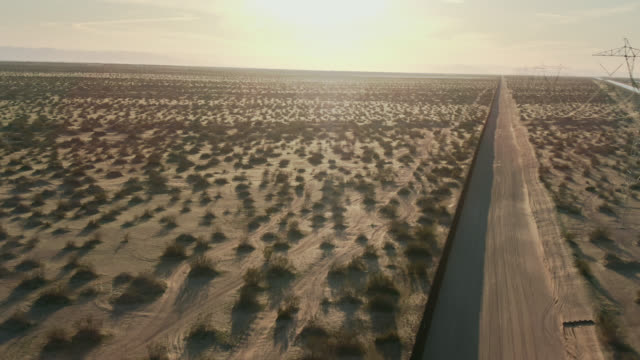aerial drone shot of a dirt road running parallel to the steel-slat border wall between mexico and the united states on a sunny afternoon in the california/mexican desert with distant mountains in the background - surrounding wall stock videos & royalty-free footage