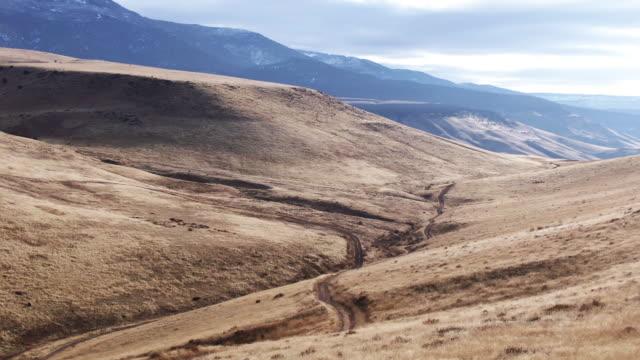vidéos et rushes de drone aérien tiré d'une route de saleté serpentant le long d'une vallée de colline couverte dans l'herbe brune à la base du grand mesa dans le colorado occidental en plein air un jour partiellement nuageux - hill