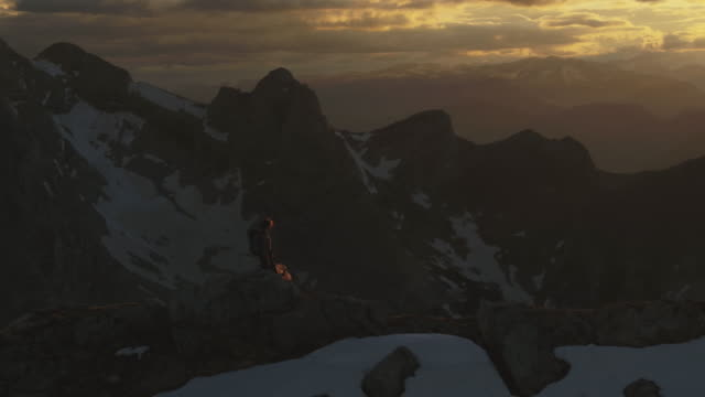 aerial drone shot of a female hiker standing on a mountain ridge at sunset - austria stock videos & royalty-free footage