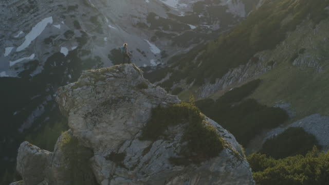 aerial drone shot of a female hiker standing on a rocky outcropping surrounded by mountains and forest - stillstehen stock-videos und b-roll-filmmaterial