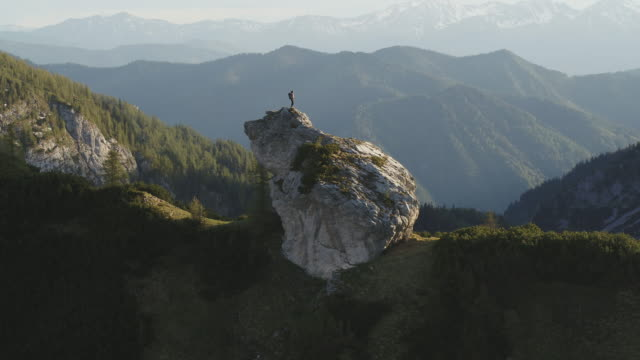 aerial drone shot of a female hiker standing on a rocky outcropping surrounded by mountains and forest - austria stock videos & royalty-free footage